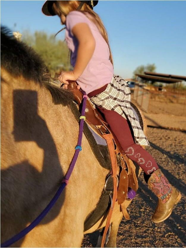 A girl learns to dismount a horse in Legend Acres virtual horse lessons